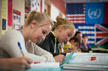 Students doing school work in front of world flags